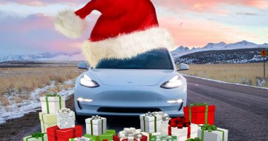 Tesla Model 3 wearing a Santa Hat surrounded by Presents