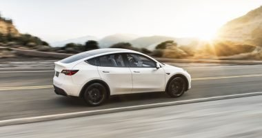 Tesla Model Y driving into the sunset